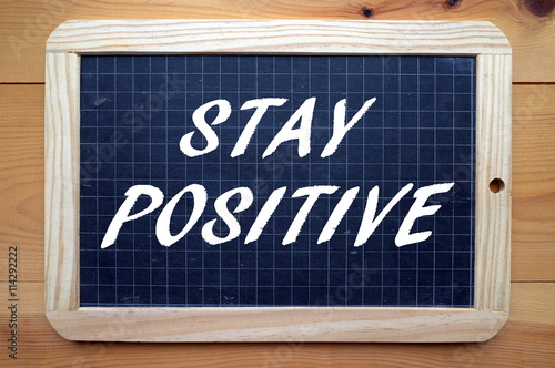 Poster The words Stay Positive written in white text on a blackboard as a reminder