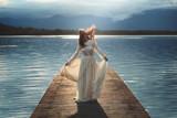 Young woman posing on lake pier - 114293054