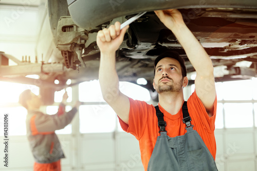 Car mechanic upkeeping car Poster