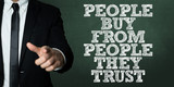 Business man pointing with the text: People Buy From People They Trust