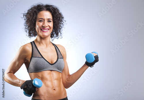fototapeta na ścianę Fit woman lifting weights on gray bakground