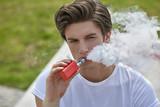 Junger Mann in T-Shirt und Jeans sitzt e-Zigarette rauchend im Sonnenschein und bläst lässig eine weiße Dampfwolke.