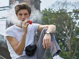 Junger Mann in T-Shirt und Jeans sitzt e-Zigarette rauchend an einer Bahnstrecke und bläst lässig eine weiße Dampfwolke.