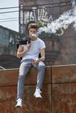 Junger Mann in T-Shirt und Jeans sitzt e-Zigarette rauchend auf einer rostigen Absperrung an einer Bahnstrecke und bläst lässig eine weiße Dampfwolke.