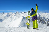 snowboarder holding board in arms raised