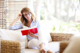 Attractive woman sitting in sofa with a book at home
