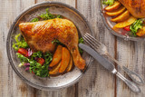 Baked chicken leg, served with roasted potatoes and vegetables. - 114407808