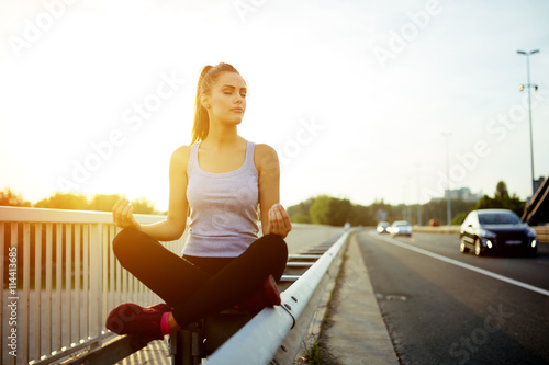 Woman relaxing next to a busy road, challenge concept Poster