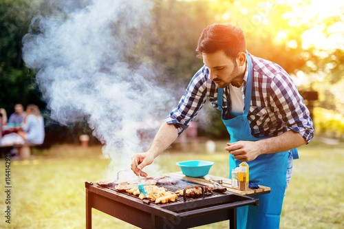 HAndsome male preparing barbecue Poster