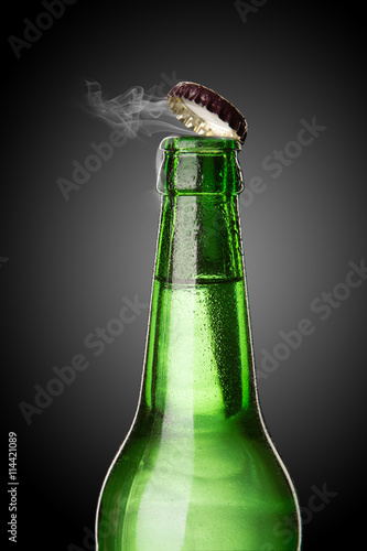 Poster Cold wet beer bottle with frost and vapor