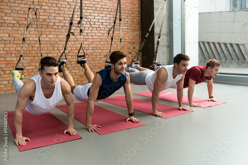 Fit four men training body in gym