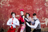 Four mimes standing in a fighting pose on a background of a red
