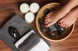 Fototapety Manicured female feet in spa pedicure procedure