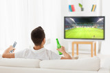 man watching soccer game on tv and drinking beer