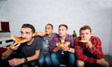 Friends watching TV with surprise, eating pizza close-up. Fans w