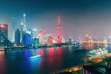 Big modern illuminated city by night. Shanghai, China. Nighttime skyline with skyscrapers and the Hunapu river.