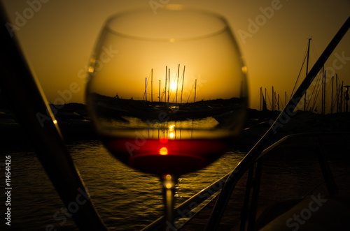 Panel Szklany Sunset over marina with fine glass of wine