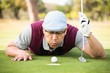 Golfer blowing ball in the hole