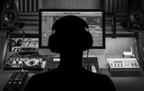 Fototapety Man produce electronic music in project home studio. Silhouette. Black and white photo.