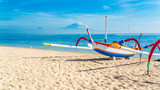 Traditional Indonesia fishing outrigger canoe on a beautiful tropical sandy beach in Bali.