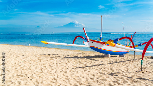 In de dag Bali Traditional Indonesia fishing outrigger canoe on a beautiful tropical sandy beach in Bali.