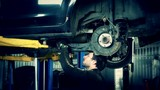 Mechanic renew brake system of a vehicle on a car lift. Zoom out.