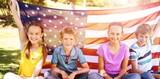 Children holding american flag in park