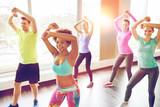 Fototapety group of smiling people dancing in gym or studio