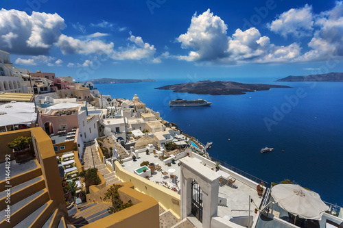 Zdjęcia na płótnie, fototapety, obrazy : Greece. Santorini (Thira). Fira town with characteristic style for Cycladic architecture - white-washed cube houses built on the edge of high cliff. There is Nea Kameni Island in the background