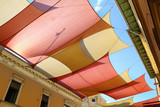 Street decorated with colored canvas awnings - 114645477