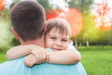 Father with his son walking outdoor. Child hugging dad