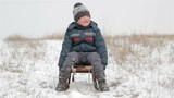 sitting on a sled in winter Boy/winter boy sitting on a sledge and snow falls