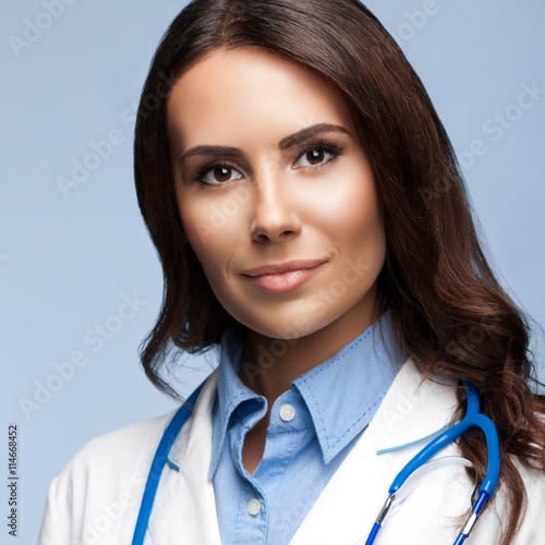 Happy smiling female doctor, on grey плакат