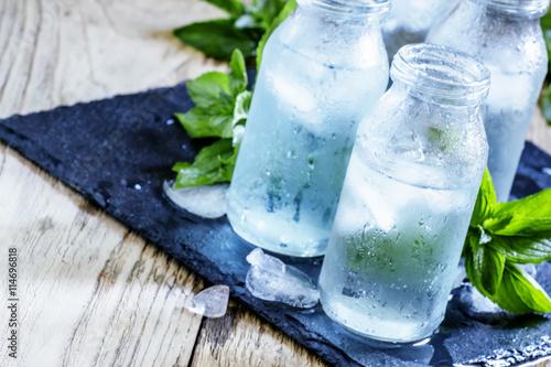 Bardzo zimna woda mineralna z lodem w zamglonych szklanych butelkach, ciemna