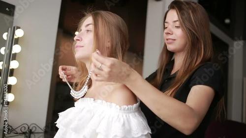 Foto op Canvas Kapsalon an employee of a beauty salon client the dress necklace. Fashion look.