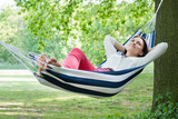 Woman Relaxing In Hammock - 114743600