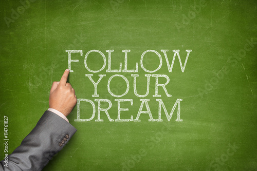Poster Follow Your Dream text on blackboard with businessman hand pointing