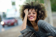 Quadro Young black woman with afro hairstyle smiling in urban backgroun