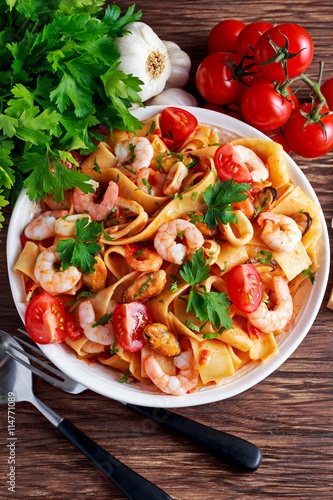 obraz PCV Tasty Pappardelle pasta with shrimp, Squid, mussel, tomatoes and herbs.