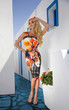 Very beautiful long-haired blonde standing woman in sexy colorful short dress in santorini in greece