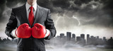 Businessman In Boxing Gloves With Cityscape In The Storm