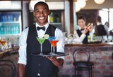 Portrait of bartender holding serving tray with cocktail glasses