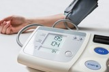 Patient suffers from hypertension. Woman is measuring blood pressure with digital monitor.