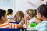 Schoolgirls gossiping in classroom