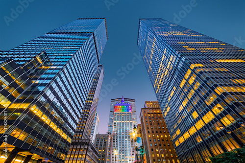 Fototapeta Upwards view of New York skyscrapers at dusk. The central building, illuminated with rainbow colors, celebrates gay pride week