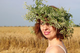 Girl in a white T-shirt with a green wreath with white flowers on the head in ripened yellow barley field
