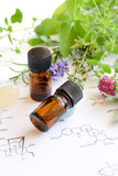 Fototapety essential oils with herbs on science sheet