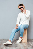 Relaxed young man in white shirt, jeans, hat and sunglasses