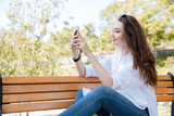Beautiful young woman with smartphone on the bench