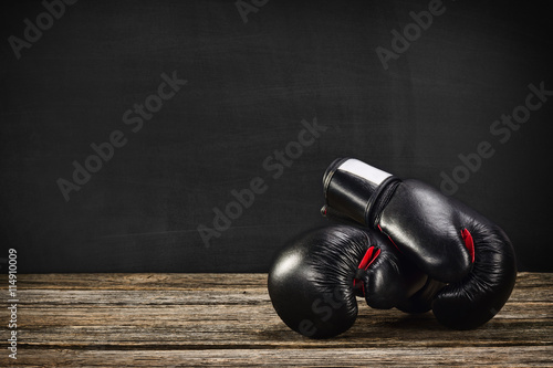 Pair of boxing gloves on a vintage wooden desk with chalkboard background Poster